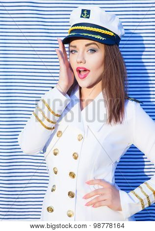 Surprised young attractive woman wearing marine captain uniform over stripy background