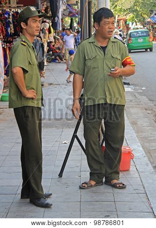 two vietnamese policemen are watching what happen on the streets