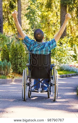 Young Man in Wheelchair with Wide Opened Arms