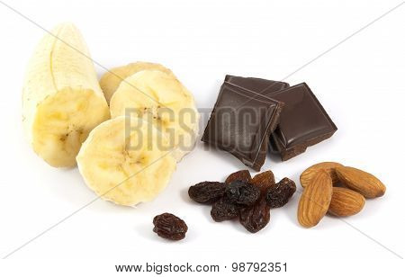 Peeled sliced banana with chocolate, almonds and raisins on white background