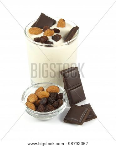 Sweet yogurt desert with chocolate, almonds and raisins on white background
