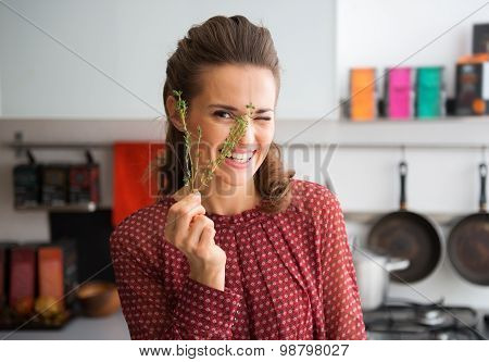 Smiling Woman Peeking Through Fresh Sprig Of Thyme