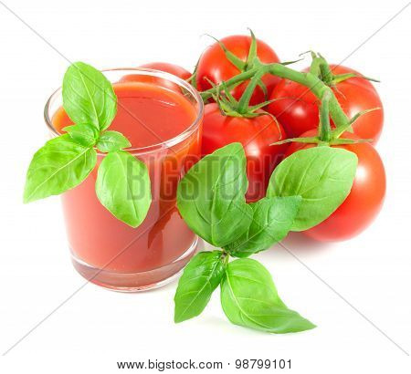 Bunch of ripe tomatoes with basil leaves and glass of tomato juice on white background