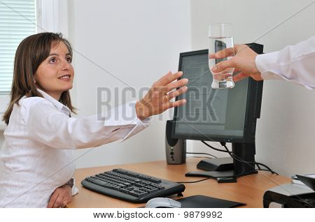 Offering Glass Of Water On Workplace