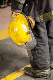 stock photo of firemen  - Low section rear view of fireman holding helmet at fire station - JPG