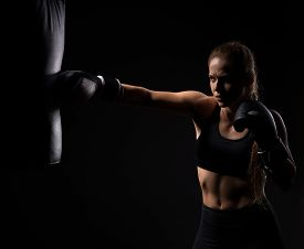 stock photo of boxing  - beautiful blonde girl in boxing gloves pushes the bag on a black background - JPG