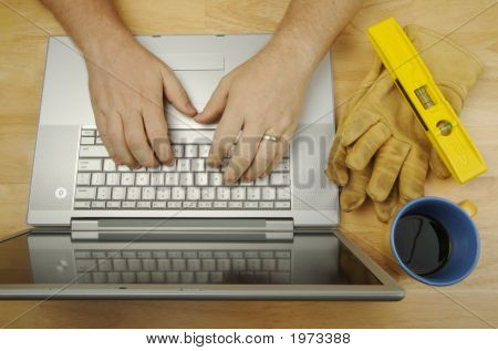 Contractor Reviews Project On Laptop