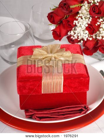 Christmas Present Resting On A Plate With Roses In The Background