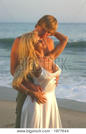 Young Couple Embraces At The Beach At Sunset.