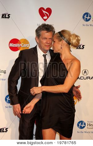 LOS ANGELES - FEB 11:  David Foster & Guest arrives at the Muiscares Gala Honoring Barbra Streisand at Convention Center on February 11, 2011 in Los Angeles, CA