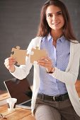 Business woman holding and pointing to a puzzle piece. Concept team. Woman. Puzzle. poster