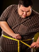 Man belly fat with tape measure weight loss around body on black background. Obesity due to eating b poster