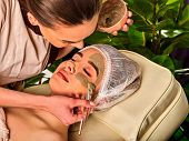 Mud facial mask of woman in spa salon. Massage with clay full face in therapy room. Therapeutic mud  poster