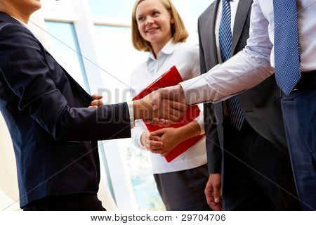 Image of business partners handshake after signing new contract