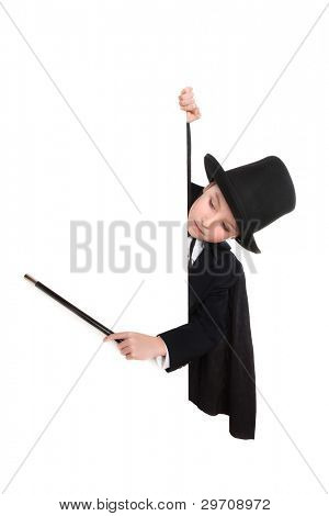 Young boy in magician costume point at a sign with his wand