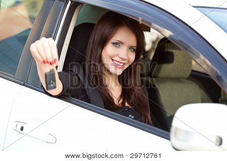 woman in car holding key
