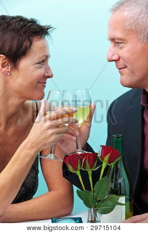 Photo of a mature married couple holding glasses of wine and looking at each other whilst sat in a restaurant.