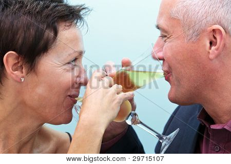 Photo of a mature married couple drinking glasses of champagne and looking into each others eyes.