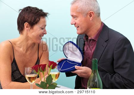 Photo of a mature man giving his wife a diamond necklace whilst sat at a table in a restaurant.