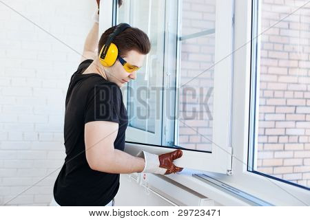 Man worker mounting window on balcony.