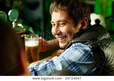 Cheerful male friends spending time together at bar and drinking beer