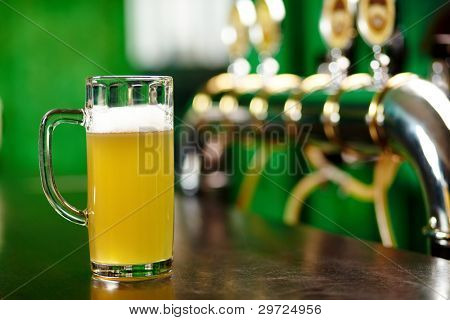 A beer pint standing on a bar counter not far from beer taps