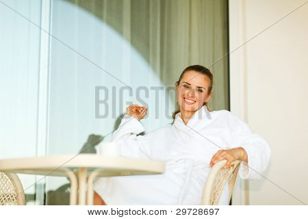 Portrait Of Smiling Woman In Bathrobe Sitting At Table On Terrac