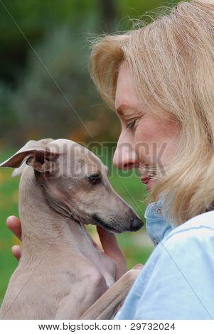 Woman cuddling dog, Italian Greyhound