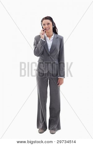 Businesswoman watching on the top speaking in a headset against white background