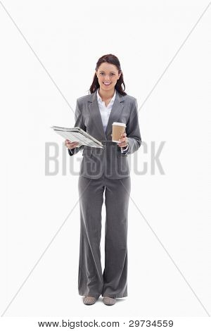 Businesswoman smiling with a coffee and newspaper against white background