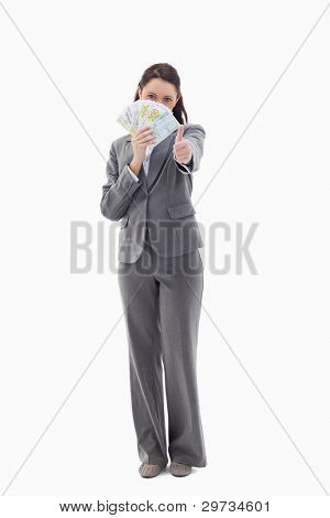 Businesswoman approving and hiding with bank notes in her hand against white background