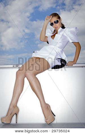 Young brunette woman in elegant dress sitting on the rooftop of a skyscraper