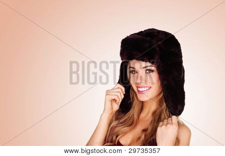 Pretty smiling girl in winter fur hat with earflaps on pastel studio background