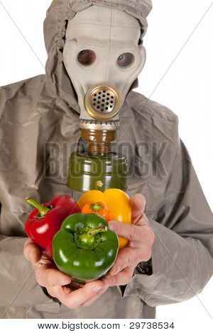 Man dressed in protection suit and gas mask is holding vegetables