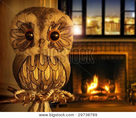 Hand-crafted fake owl perched on a branch in an inviting warm home setting with big window and glowing fireplace