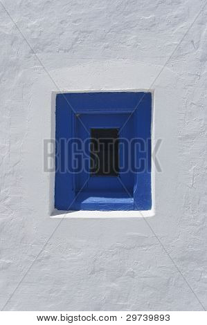 Greek blue window in white-washed wall