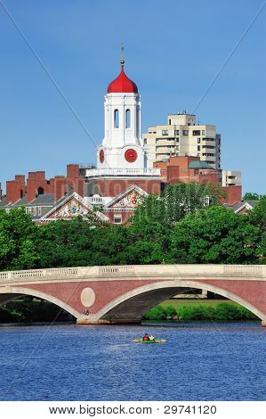 John W. Weeks Bridge and clock tower over Charles River in Harvard University campus in Boston with trees, boat and blue sky.