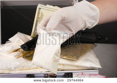 Cocaine and marijuana with gun in a suitcase with hand holding a package of cocaine closeup