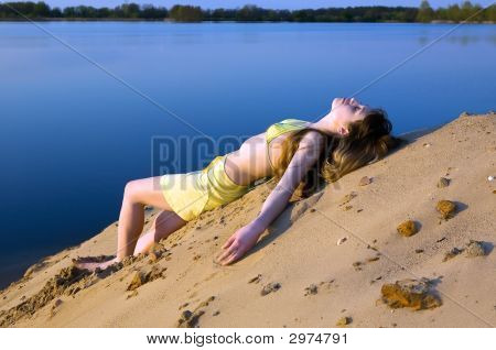 Blond Girl Lying On The Beach