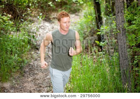 Handsome man running in forest against blur background