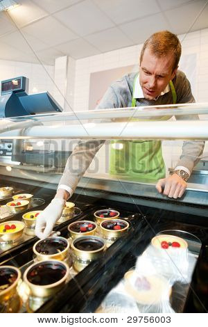 A man selling gourmet deserts from behind a glass counter