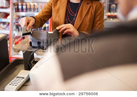 Shop assistant swiping credit card in supermarket with customer in the foreground