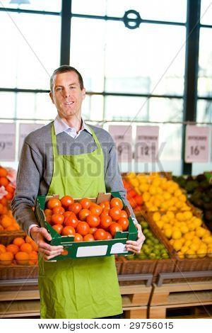 einen freundlichen Supermarkt-Besitzer mit einem Kasten reife Tomaten