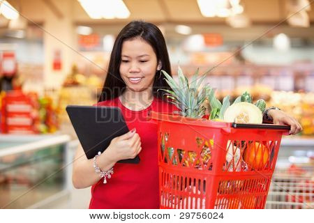 Smiling woman looking at digital tablet and holding fruit basket in shopping centre