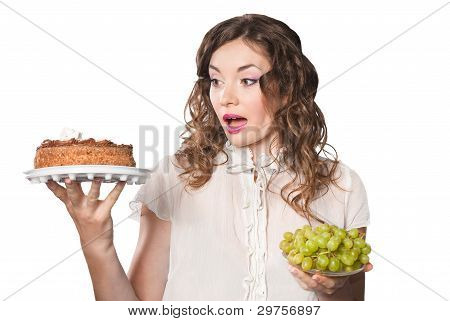 Young Woman Choosing Between Cake And Grapes Isolated On White Background