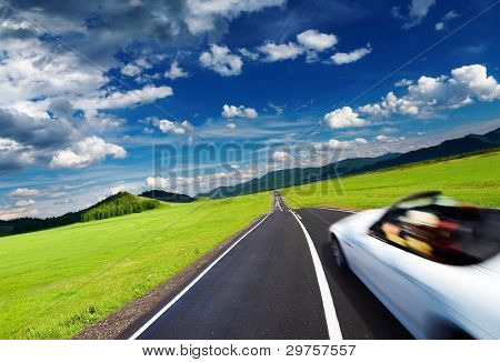Mountain landscape with road and moving car
