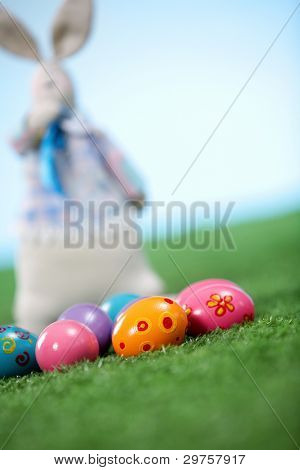 Tilt up shot of Easter eggs and a toy bunny in the background