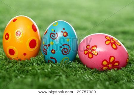 Three easter eggs lying on the lawn