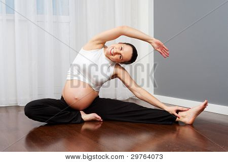 healthy pregnant woman doing gymnastic at home