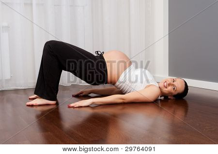 portrait of healthy smiley pregnant woman doing exercise at home